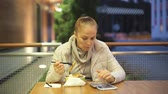 cena urbana : a middle-aged Caucasian woman is sitting at a table in a summer cafe on a cold evening, eating vegetable salad and fried chicken, next to her is a smartphone and a tablet.