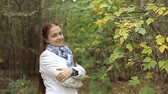 idade média : red-haired Caucasian middle-aged woman in a white coat walks on a cloudy day in the autumn park