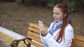 red-haired middle-aged woman with a smartphone in her hand sits on a bench in the Park and communicates in social networks