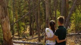plaid : a young couple walks in a pine forest on stone rocks on a bright Sunny day.