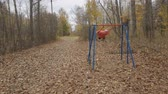 girl riding on a swing in the autumn Park Stock Footage