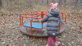 little girl playing in the autumn Park on the carousel Stock Footage