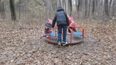 two sisters and a brother play in the autumn Park. Children ride the carousel
