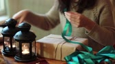 string : Young Woman Wrapping Christmas Gifts With Brown Paper At Home