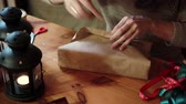 подарок : Young Woman Wrapping Christmas Gifts With Brown Paper At Home