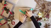 string : Top view woman wrapping christmas presents With Brown Paper At Home Stock Footage