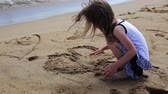 inspirar : Little girl drawing and jumps on the shore of a sand beach. Vídeos