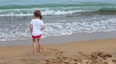 caminhada : Little  Girl playing with waves at the beach in clothing
