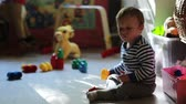 months : Little cute boy playing with toys on the floor in the nursery Stock Footage