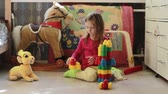 desenvolver : Cute little girl playing with toy blocks at home in the morning Stock Footage