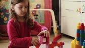 выстрел : Cute little girl playing with toy blocks at home in the morning Стоковые видеозаписи