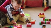 игривый : baby boy playing with his sister with toys on the floor in the nursery