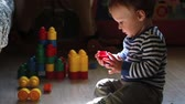 bloco : Little cute boy playing with toys on the floor in the nursery Stock Footage