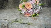 cores : Wedding rings and wedding bouquet on stone