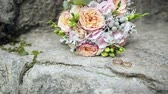 casamento : Wedding rings and wedding bouquet on stone
