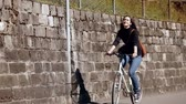 muro de pedras : Girl riding a bike on the street past the stone wall