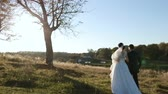 novomanželka : Beautiful young couple bride and groom in a wedding dress at sunset in the park holding hands