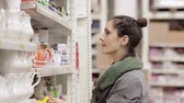 supermarket : Young woman chooses shelves in the supermarket
