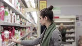 iogurte : Young woman chooses dairy produce in the store Stock Footage