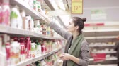 atraente : Young woman chooses dairy produce in the store Stock Footage