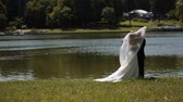 margem do rio : bride and groom standing by the river. slow motion