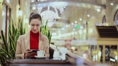 mensagem : Woman using smartphone, drinking coffee in cafe.