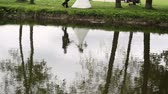 margem do rio : Reflection of the bride and groom in the water Stock Footage