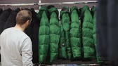 мода : Middle-aged man chooses a warm jacket in store