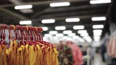 cabide : Various clothes on hangers in a store. slider shot Stock Footage