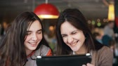irmã : two girls sisters using tablet talking in cafe