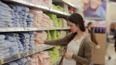 cal : Young woman chooses towels in the supermarket Vídeos