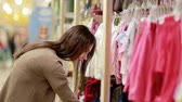 мода : young woman chooses clothes for newborn baby