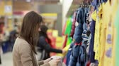 cabide : young woman chooses clothes for a child Stock Footage