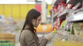 corredor : Girl selects the candy on the shelves in the store Vídeos