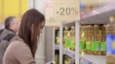 консервы : Young woman chooses sunflower oil in the store Стоковые видеозаписи