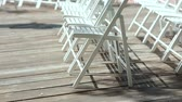 сиденья : White chairs on a wooden platform in the open air