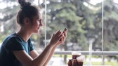 bruneta : Woman using smartphone sitting near the window Dostupné videozáznamy