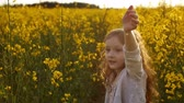 close up : Girl standing amidst of field at sunset. Slow mo