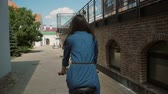 фокус : Back view of a girl in a dress riding a bike with flowers in basket in the street in summertime, slow mo, steadicam shot