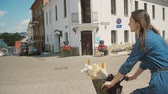 фокус : Back view of a girl in a blue dress riding a bike with flowers in a basket in the street, slow mo, steadicam shot