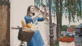 contraste : Brunette girl touching her hair, taking selfie, standing with a bike with flowers and bread in a basket, slow mo