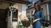 głowa : Beautiful brunette smiling girl wearing sunglasses standing near cute building with a bike talking on the phone, slow mo