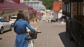 contraste : Back view of a girl with waving hair walking her bike with flowers and bread in a basket, 4k steadicam shot