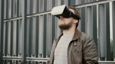 interativo : bearded attractive man uses virtual reality glasses in the urban space. 4k
