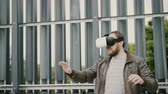 topo : bearded attractive man uses virtual reality glasses in the urban space. 4k