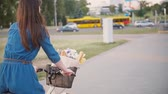 francês : Side and back view of a girl riding a bike with flowers and French bread in basket in the city, slow mo, steadicam shot