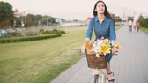 close up : Brunette girl cycling with flowers in a basket and exploring the city, slow mo, steadicam shot