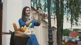 pão : Brunette girl touching her hair, taking selfie, standing with a bike with flowers and bread in a basket, 4k Vídeos