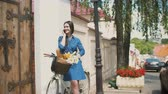bisikletçinin : Beautiful girl standing in the street with a bike with basket talking on the phone and smiling, 4k Stok Video