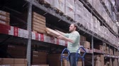 checagem : A man is taking a box from a shelf, putting it on the trolley in a warehouse
